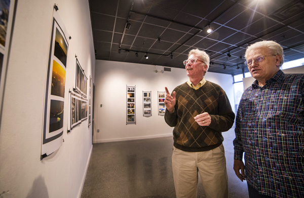 Two men standing next to each other looking at pictures in a photo exhibit