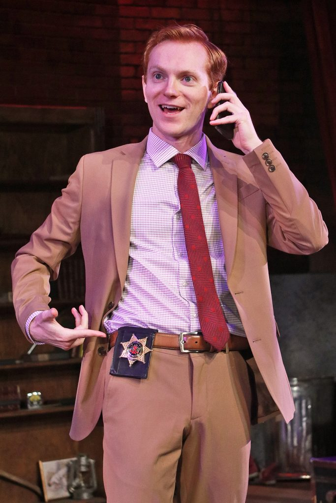 Man wearing a light brown suit, brown belt, blue and white checkered shirt, and a red tie holding a phone to his ear pointing to a police badge on his belt