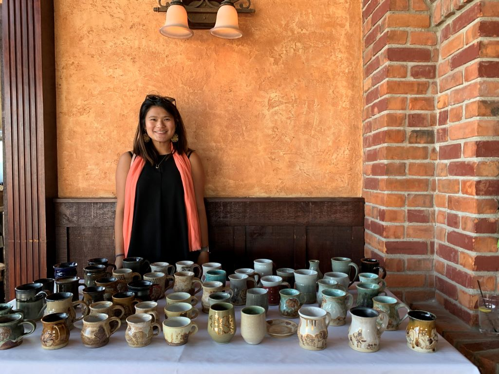 Woman with dark hair standing in front of a table with several small pieces of pottery