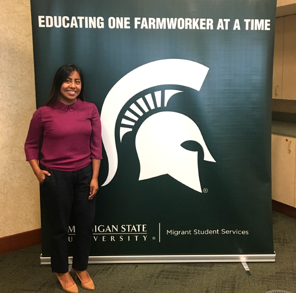 woman with black hair wearing a purple shirt and black pants is standing next to a poster with the MSU spartan logo