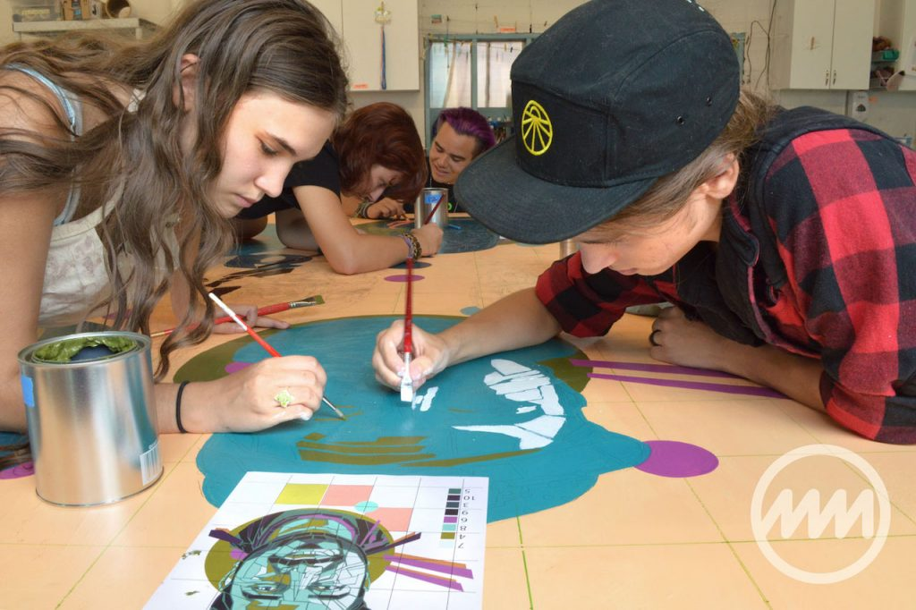 students hovered around a table and painting