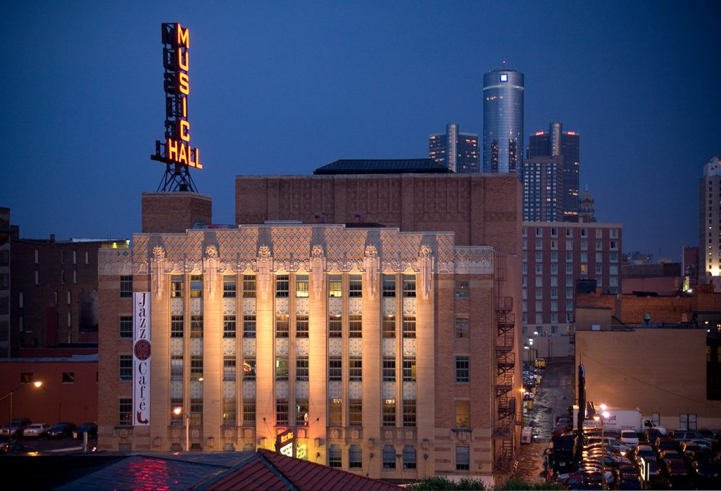 """old building made with light stone with a large neon sign that says """"music hall"""" above it at night"""