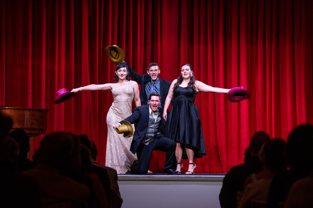 group of four people who are dressed in formal attire and are holding colorful hats in the air in front of a red curtain