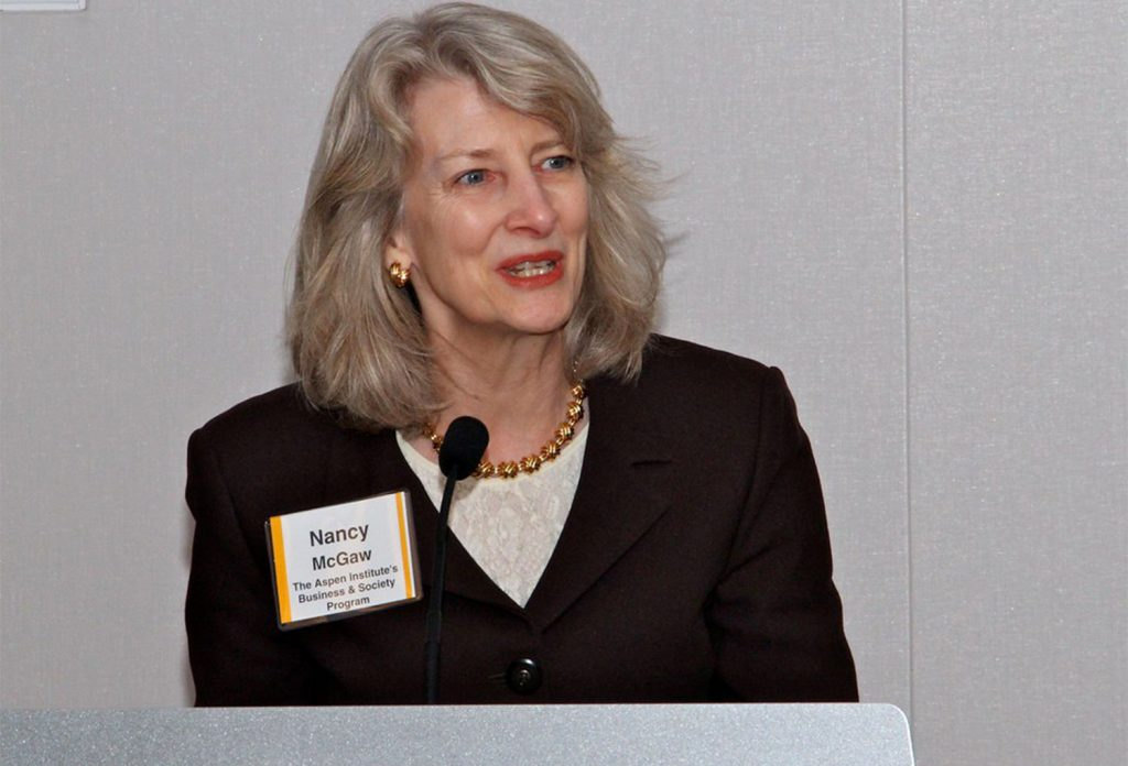 Woman with short blonde hair speaking into a microphone and wearing a gold necklace, a white shirt, and a black blazer with a name tag on it
