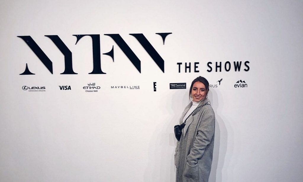Photo of person wearing grey coat with white shirt and black purse standing in front of white wall that says 'NYFW The Shows'
