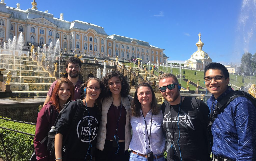 group of people smiling for a picture in front of white buildings in Russia