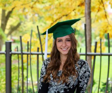 woman with a msu green graduation cap and long brown hair, she is wearing a patterned black top