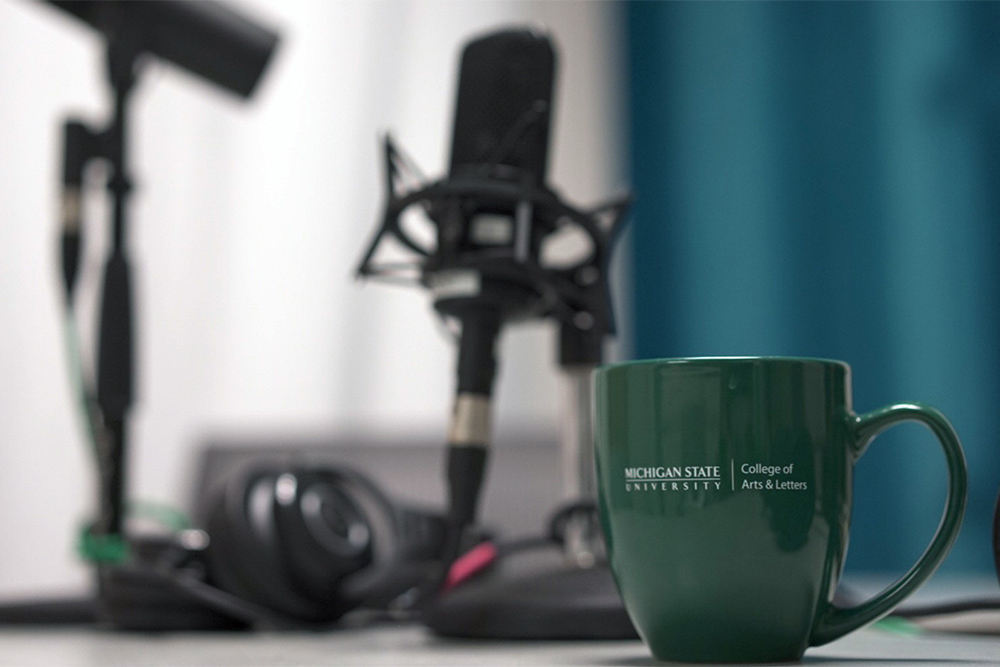 green college of arts and letters mug in front of podcast mic