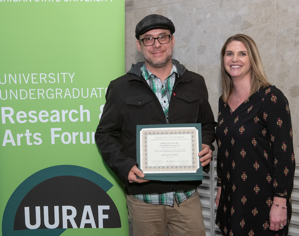 Photo of two people standing next to each other with the left person holding a certificate
