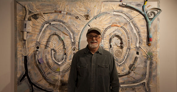 man in hat and glasses stands in front of his artwork