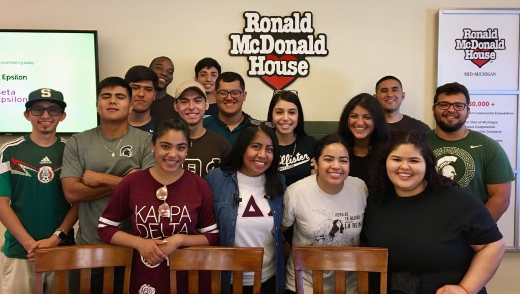 Group of people posing in front of a sign that reads 'Ronald Mcdonald House'
