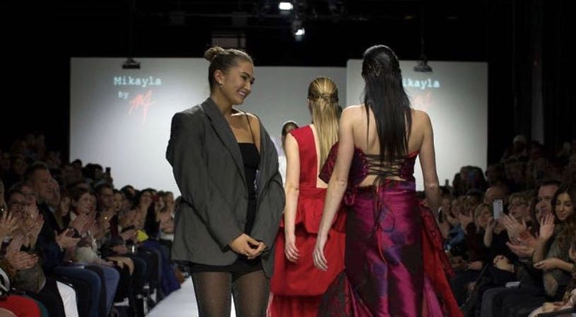 Photo of people walking down a runway with one smiling at the audience