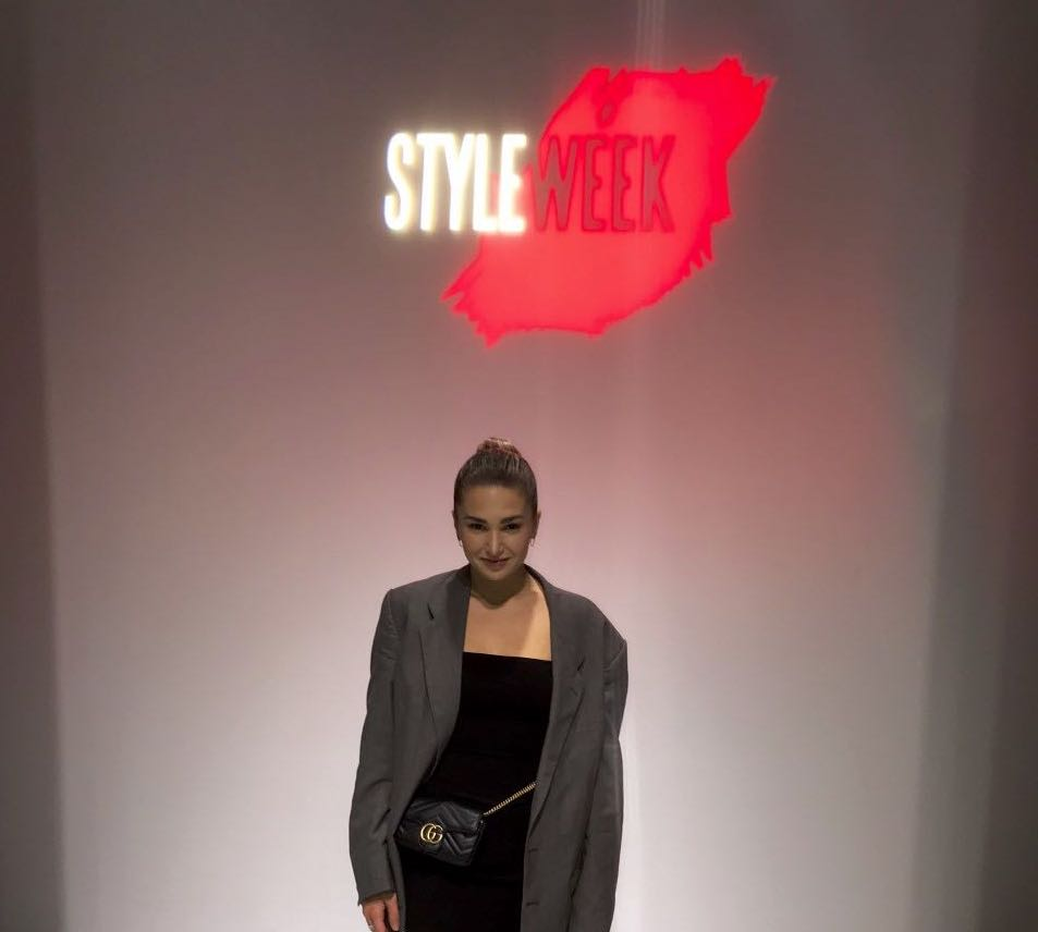 Photo of person wearing a black dress with a grey blazer and a black purse standing in front of a wall that says StyleWeek