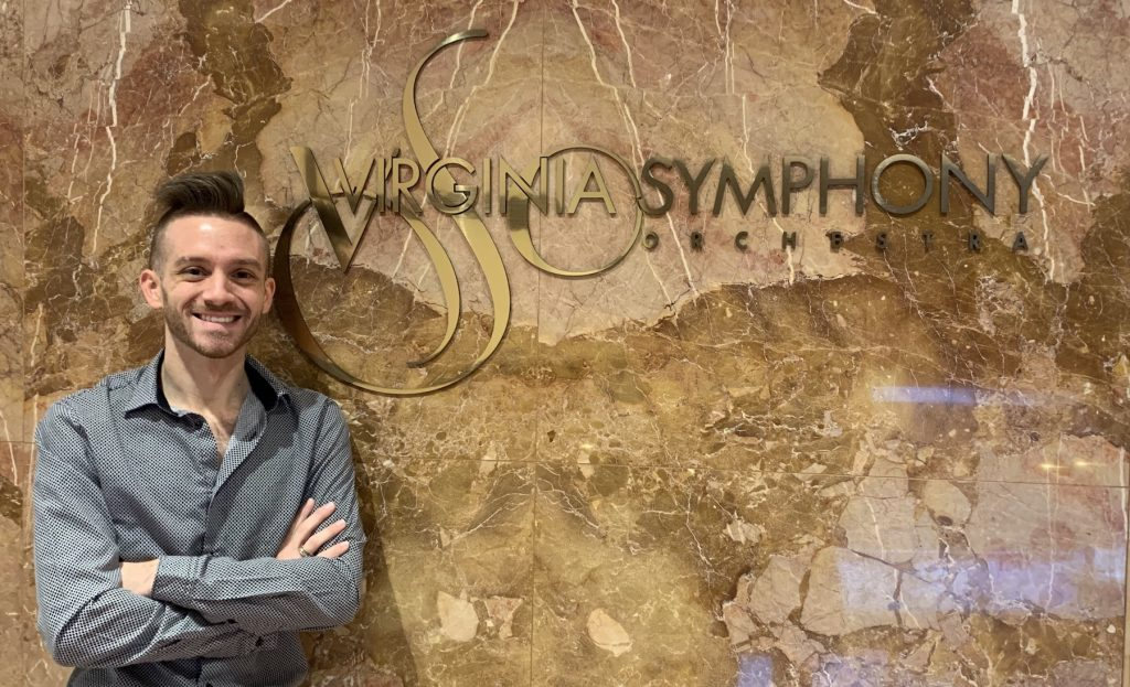 """A man with blonde hair is standing with his arms crossed over his chest in front of a granite wall that reads, """"The Virginia Symphony"""""""