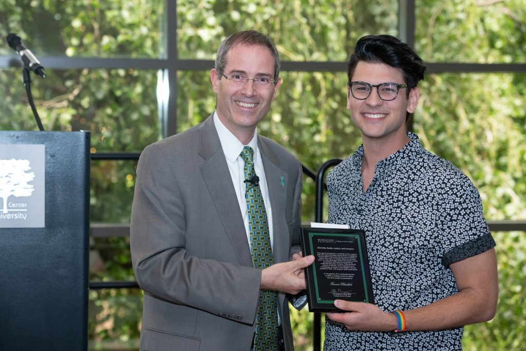 a man in a grey suit coat with a white shirt and green neck tie and a man with dark hair wearing glasses in a white button down holding an award