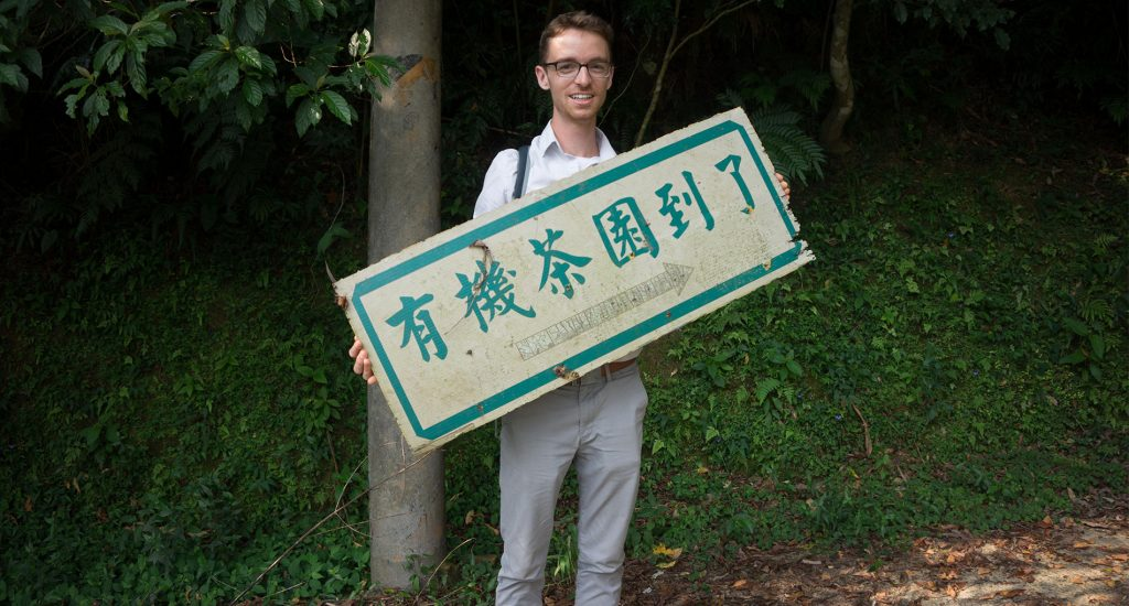 Man wearing gray pants holding a sign in front of greenery