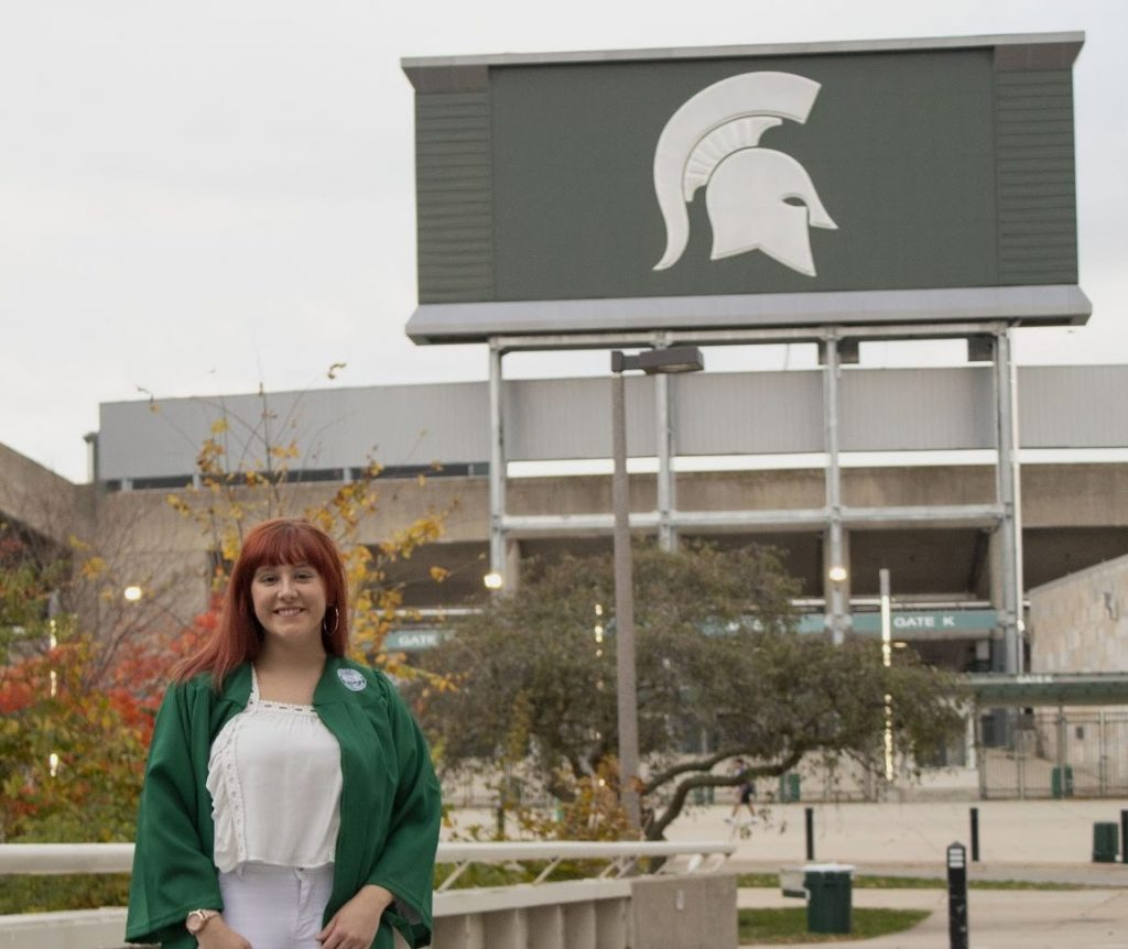 a women in green robes standing in front of the spartan stadium