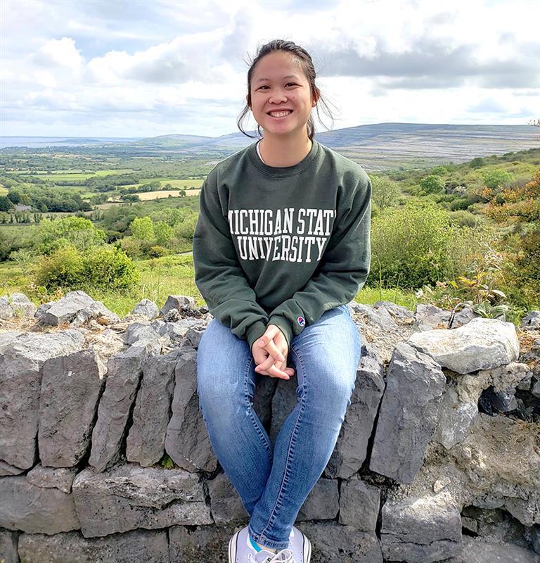 a girl in an MSU sweatshirt sitting on a rock wall