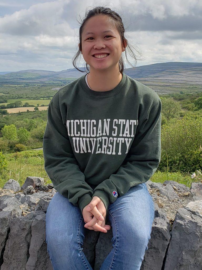 woman wearing a Michigan State University sweatshirt and jeans sitting on a stone wall