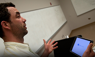 man lecturing while holding tablet