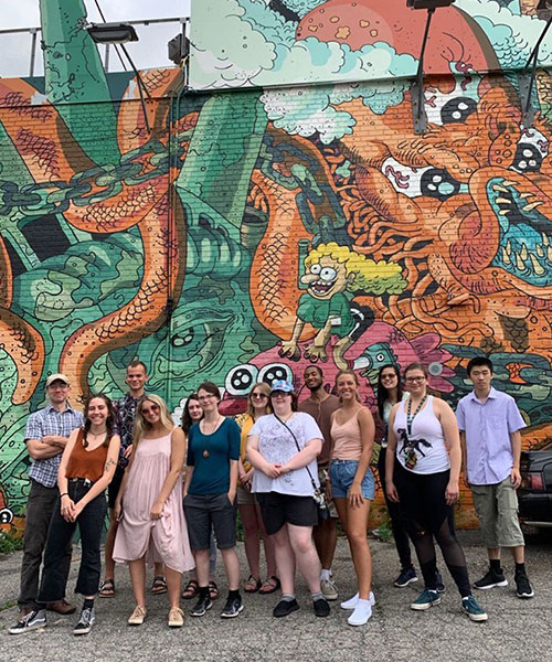 Group of thirteen people in from of a mural with a dragon on it