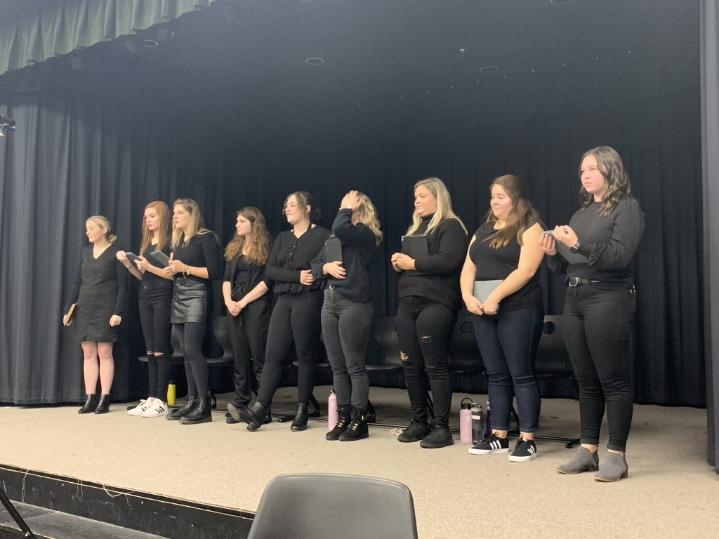 nine women wearing all black standing on a stage