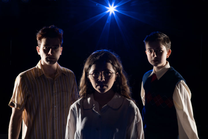 Two boys and a girl standing in the dark with a blue light shining on them