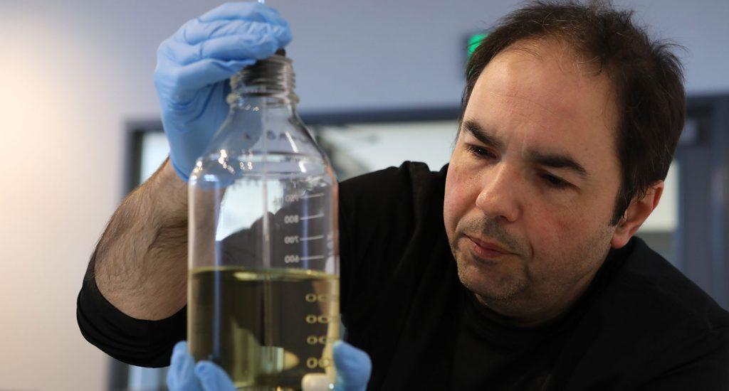 a man with dark hair wearing blue latex gloves in a black long sleeve shirt holding a liquid