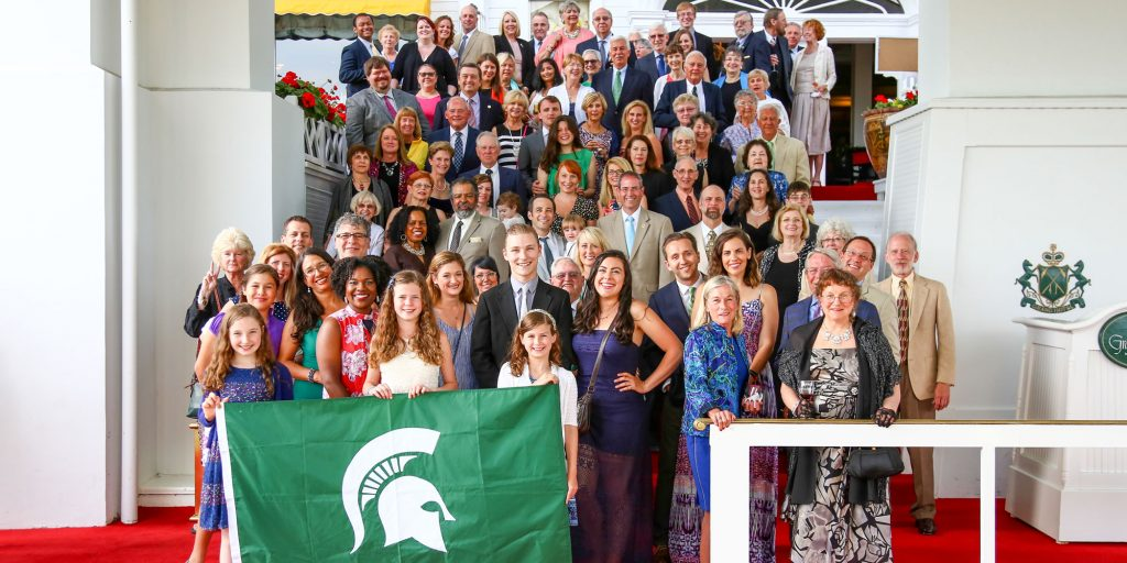 arts weekend attendees posing with spartan flag