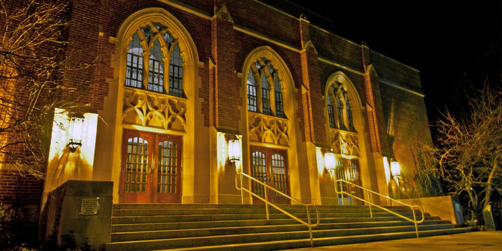 photo of a red, brick building with three entrances and big windows above the doors at night