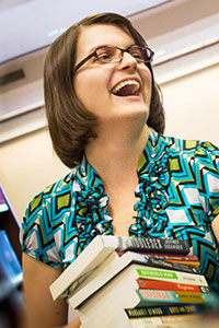 woman with short brown hair and light blue shirt holding books and laughing