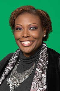 close up of woman with short brown curly hair wearing a grey shirt and floral scarf smiling with green background