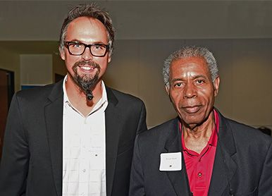 man with glasses poses with man with gray hair