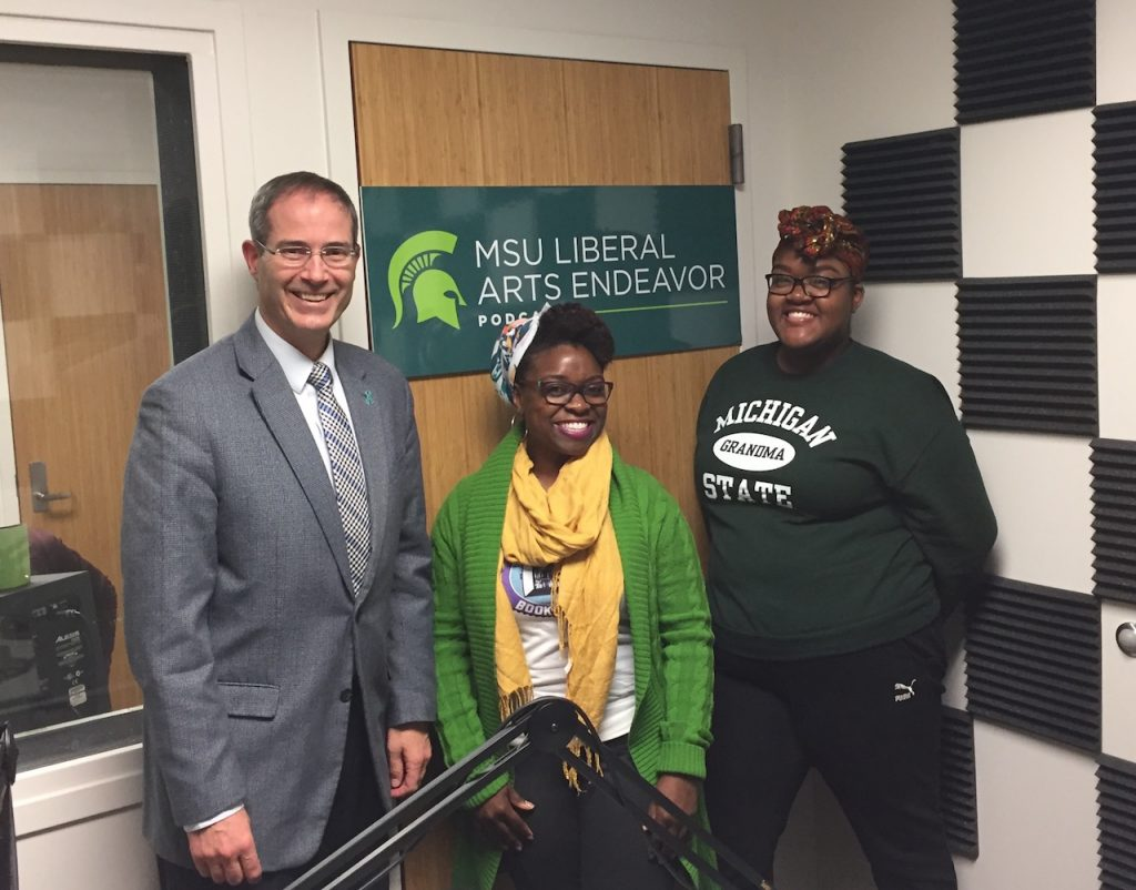 photo of two women and one man who are standing inside in front of a green sign that says MSU Liberal Arts Endeavor Podcast