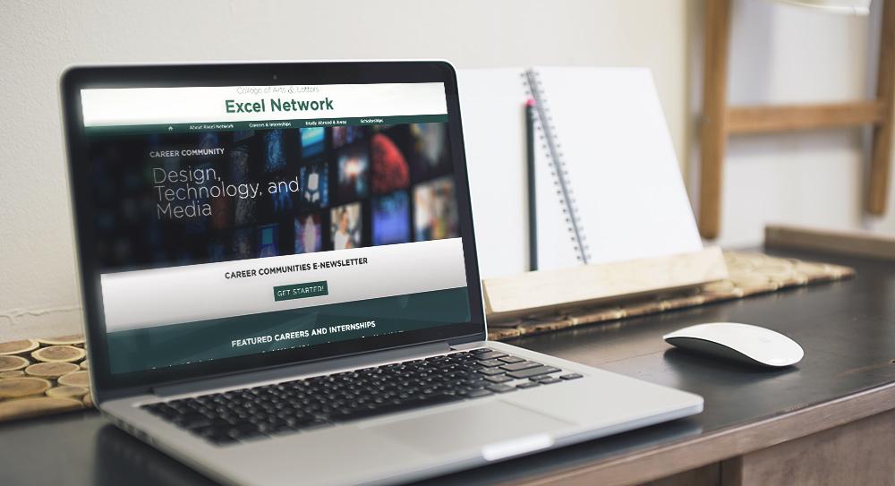 laptop on desk displaying excel network website homepage