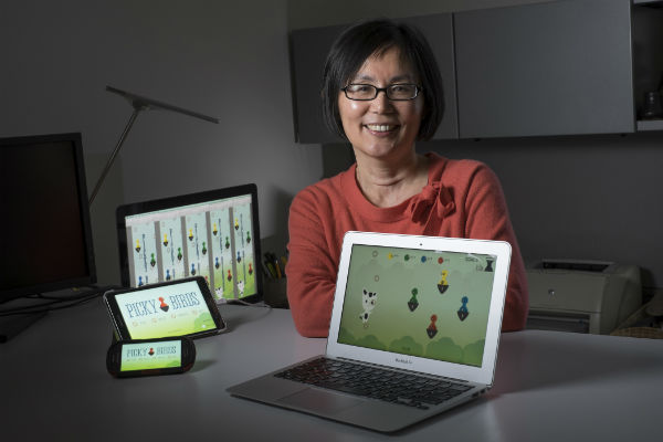 A woman in a red sweater smiling with several electronic devices displaying a game called picky birds