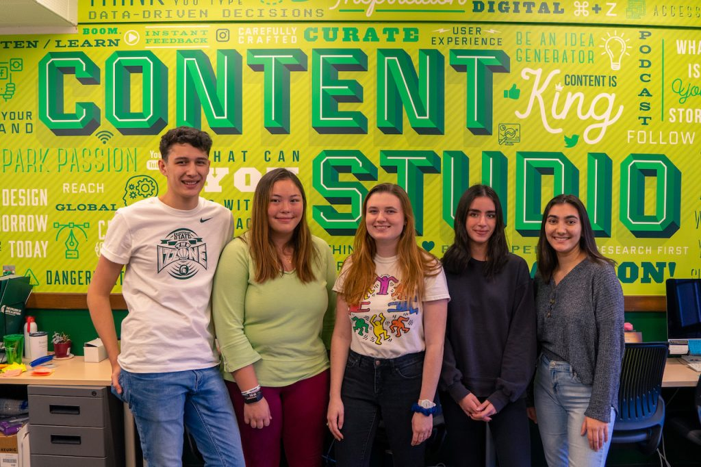 a group of students standing in front of the content studio wall