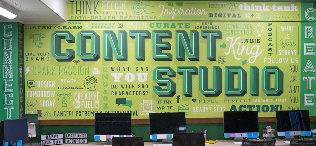 Green wall in an office that says 'content studio' and has graphics of words around it