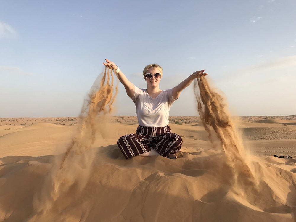 a girl in a white shirt and red pants sitting in the sand