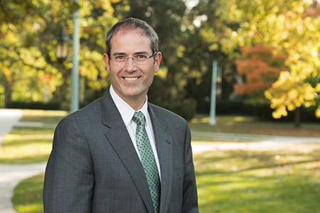 a man wearing glasses, a gray suit, and a green tie with trees in the background