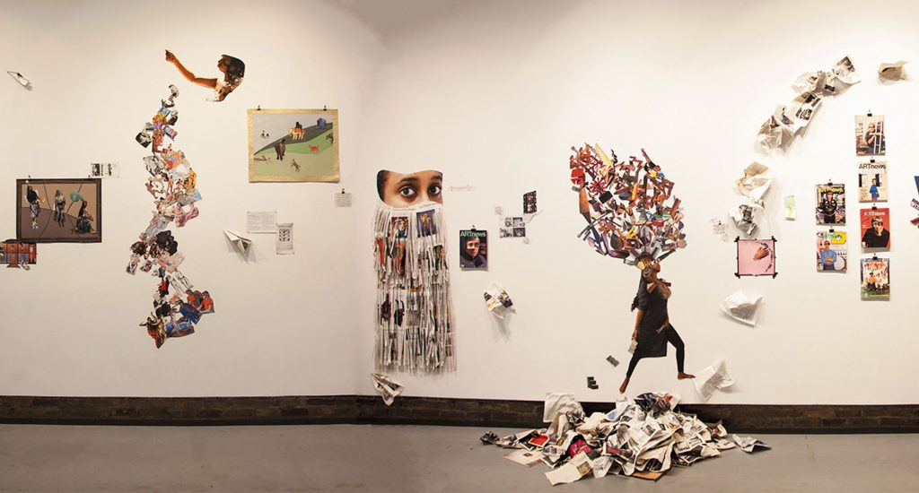 White wall with different, colorful art installations on it.