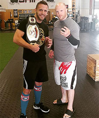 two men wearing gym shorts and t-shirts, one is holding a wrestling belt