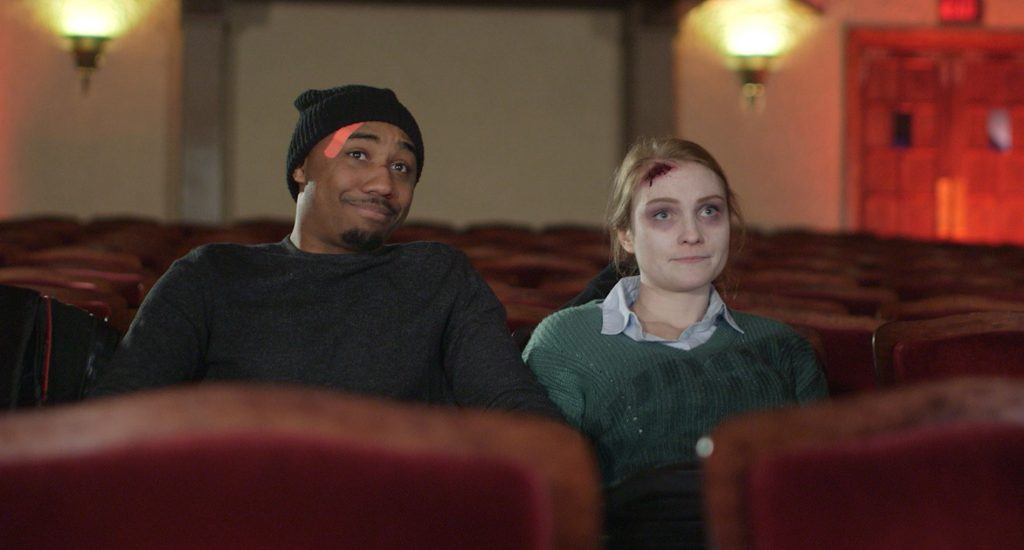 Man (left) wears a black beanie and black sweatshirt and has a bandaid on his face. Next to him sits a woman with blonde hair, purple bags under her eyes, and a gash on her forehead. She is wearing a green sweater. The two sit in a movie theatre.