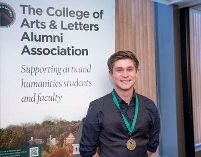 "man with brown hair wearing medal posing next to ""The College of Arts & Letters Alumni Association"" sign"