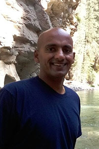 man who's wearing a navy blue shirt and standing in front of large rocks and a body of water