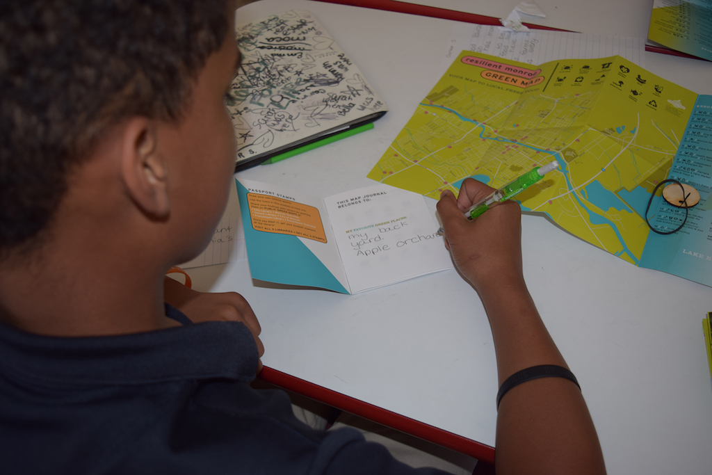 child writing in a small booklet next to a large green map