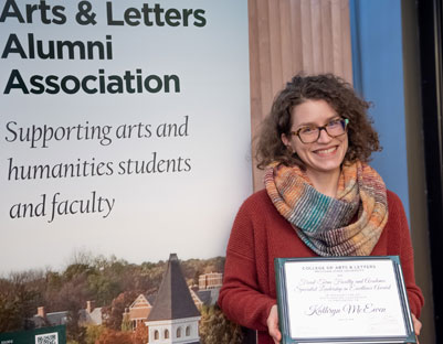 "woman with glasses and scarf holding award posing next to ""The College of Arts & Letters Alumni Association"" sign"