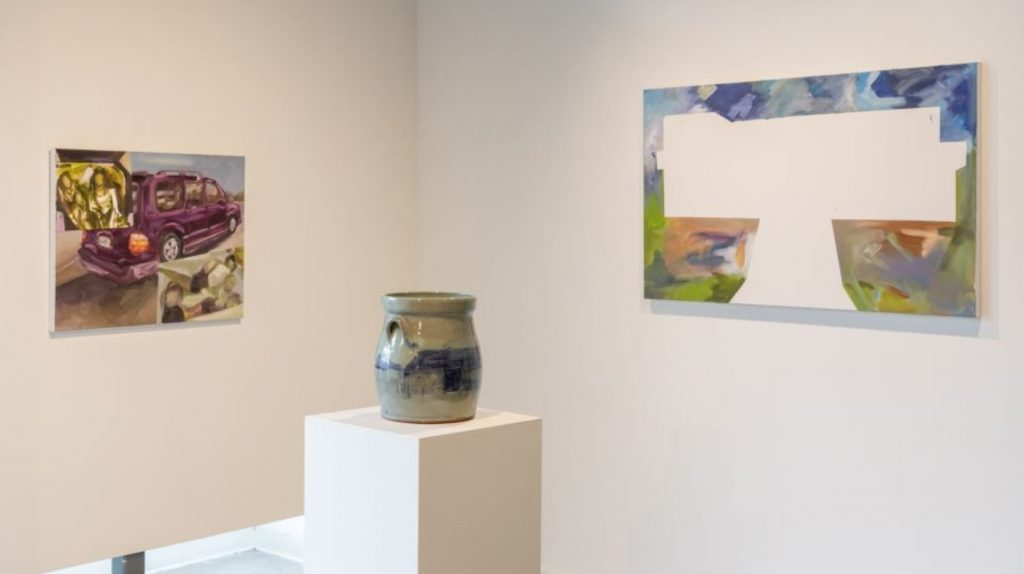 art gallery with two paintings and a ceramic work in the center