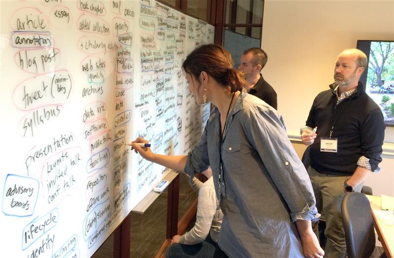 Woman with brown hair in a low ponytail wearing a jean shirt writing on a whiteboard filled with words. Behind her are two men wearing black sweaters looking at the whiteboard
