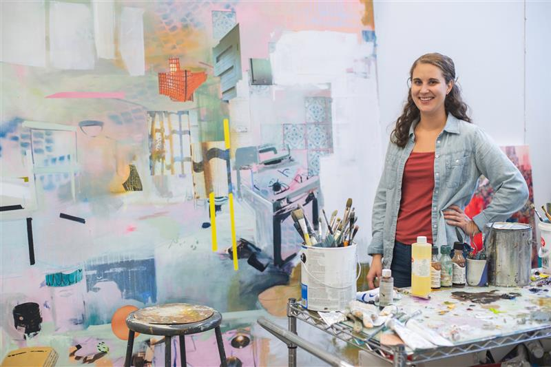 full body portrait of a girl with brown hair wearing jeans, a pink tank top and a blue button up shirt standing in front of a painting